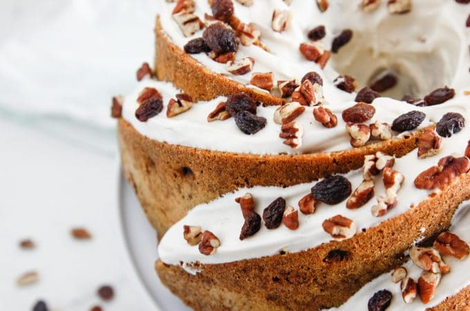 Maple Cream Cheese Carrot Bundt Cake is decorated beautifully with frosting, nuts and raisins.
